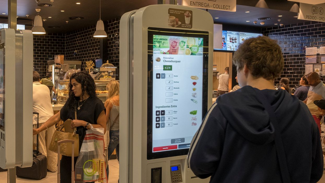 Man ordering food at McDonald's self-serve kiosk