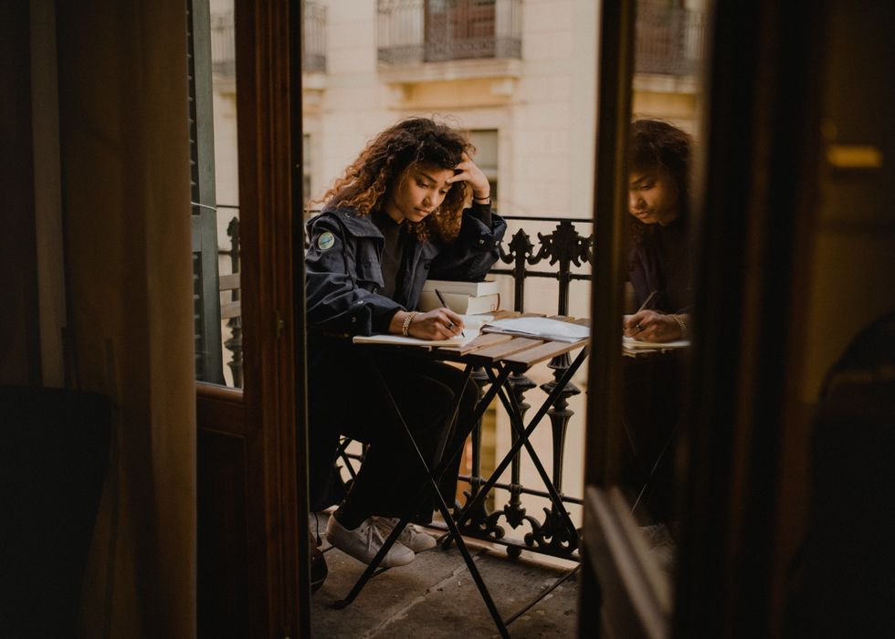 Girl writing in a journal outside