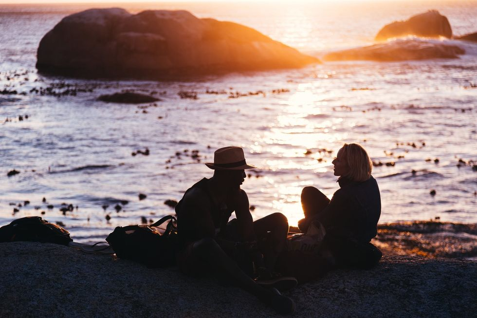 https://www.pexels.com/photo/man-and-woman-sitting-on-shore-near-body-of-water-during-sunset-1330808/