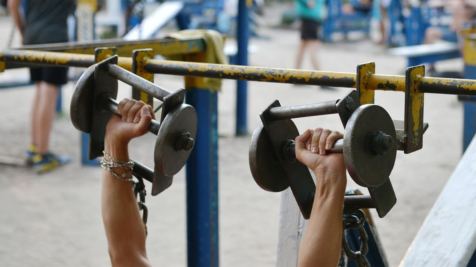 A person lifts dumbbells on August 18, 2017 at an open air gym in Ukraine's capital Kiev. (Photo by Genya Savilov/AFP/Getty Images)