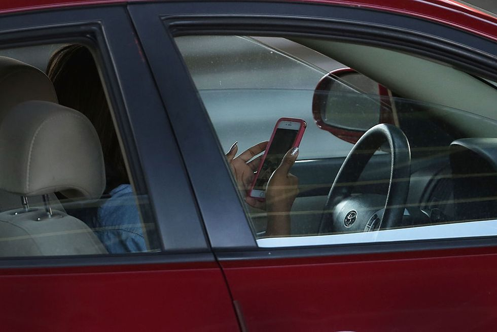 A driver uses a phone while behind the wheel of a car on April 30, 2016 in New York City. (Photo by Spencer Platt/Getty Images)