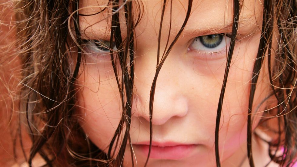 An angry kid young girl with glaring eyes stare