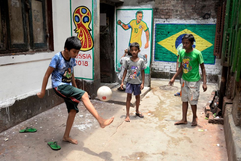 Indian boys play football or soccer barefoot in a narrow lane of Kolkata in front of Brazil flag and player Neymar (Jr.) painted on wall on the occasion of FIFA World Cup 2018. (Photo by Saikat Paul/Pacific Press/LightRocket via Getty Images)
