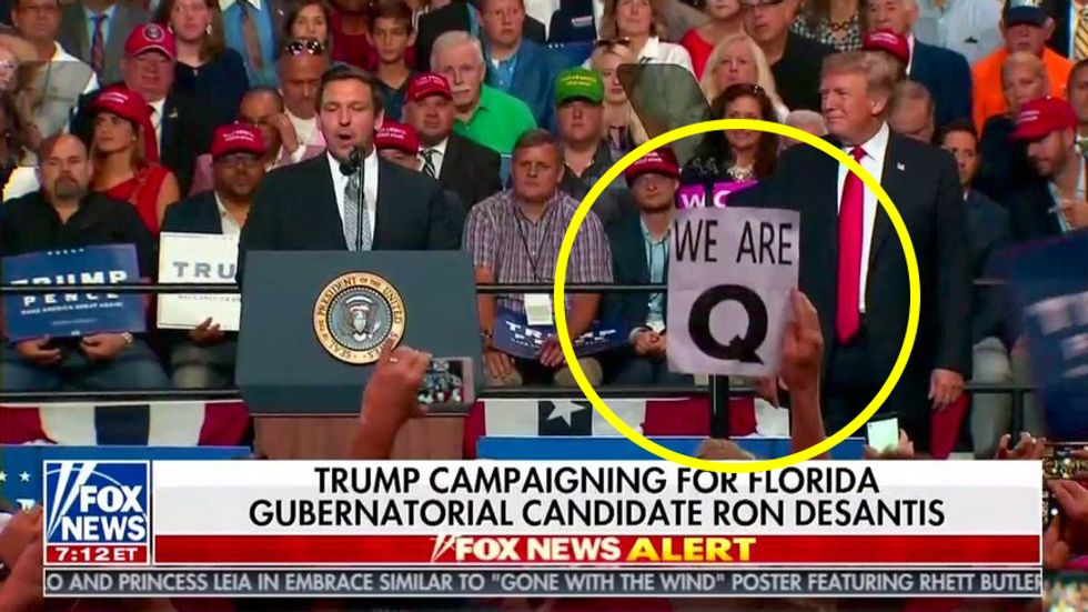 "What is QAnon? People hold a ""We are Q"" sign at Trump rally."
