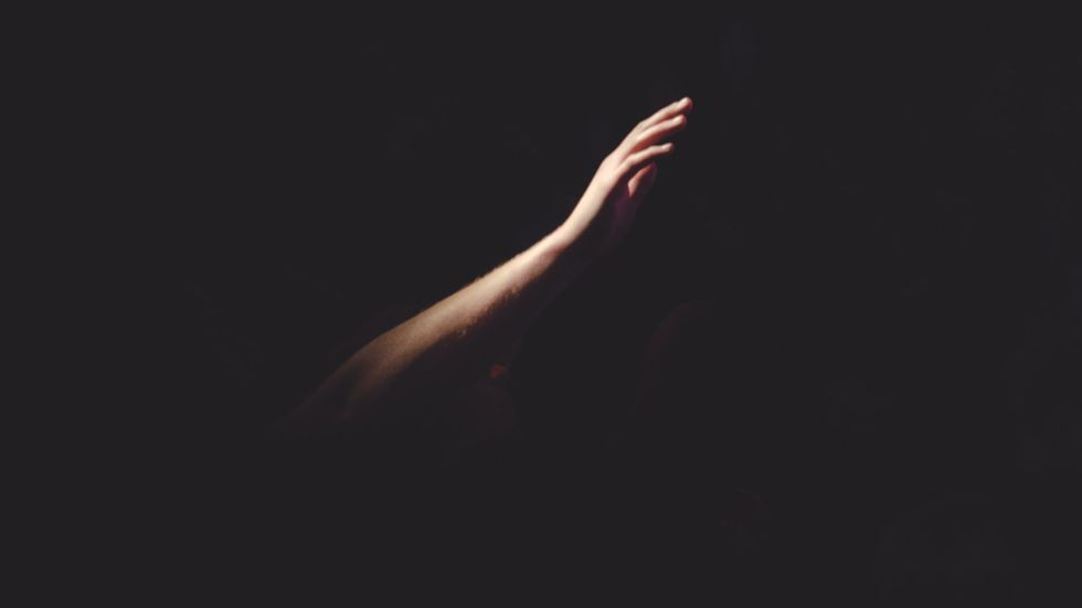 A depressed person with their arm reaching out in the blackness. Photo by Cherry Laithang on Unsplash