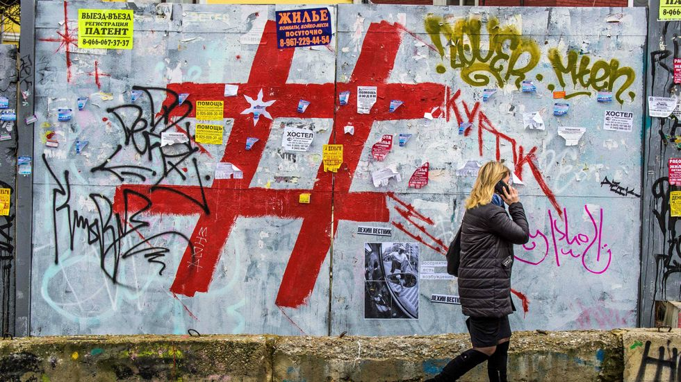 A woman speaks on a mobile phone as she walks past a graffiti covered wall with a giant hashtag sign near Moscow's Kursky railway station on November 17, 2017. (Photo: MLADEN ANTONOV/AFP/Getty Images)