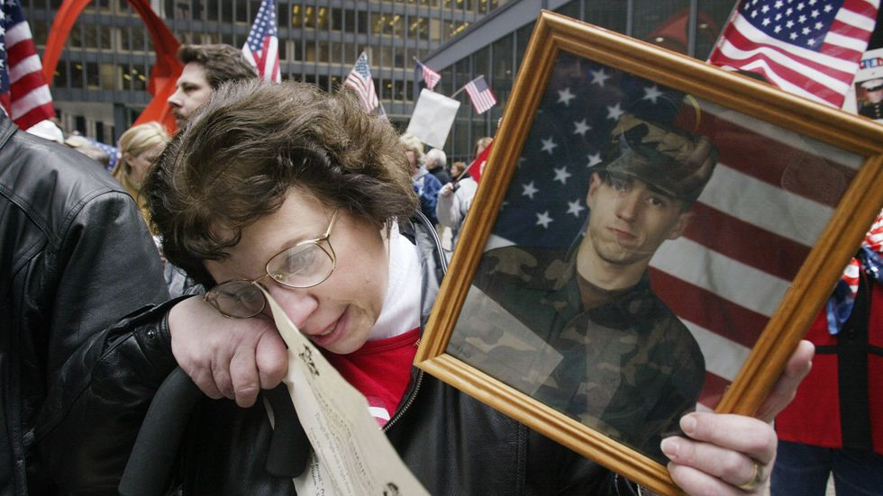 Claire Tortorello, holding a photo of her son Greg, wipes a tear from her eye following the singing of a patriotic song during a war protest March 22, 2003 in downtown Chicago, Illinois. (Photo by Scott Olson/Getty Images)