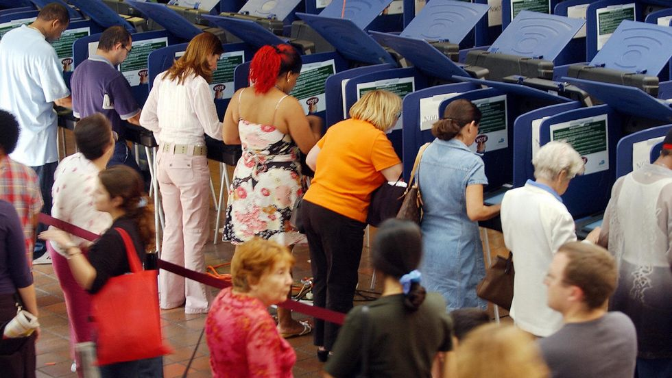 Residents of Dade county, Florida, use electronic voting machines to cast their votes at a local polling station 29 October 2004, in Coral Gables, Florida. (Photo credit ROBERTO SCHMIDT/AFP/Getty Images)