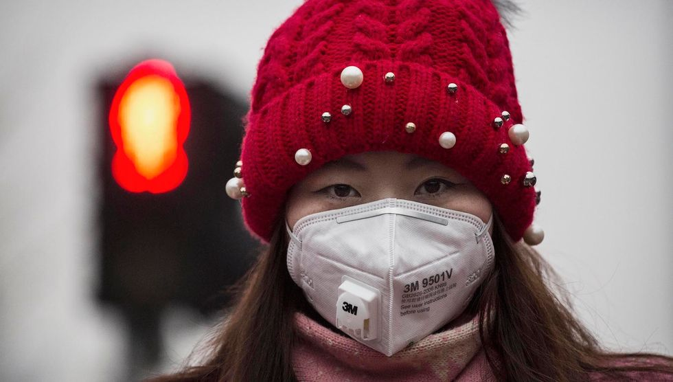 A Chinese woman wears a mask to protect against pollution as they wait to cross the street in heavy smog on December 8, 2015 in Beijing, China. (Photo by Kevin Frayer/Getty Images)