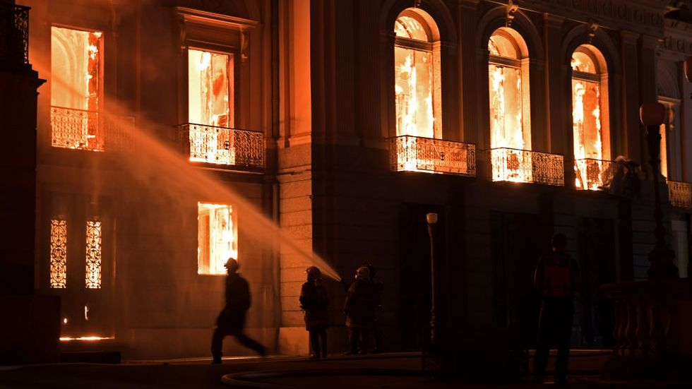Firefighters work as a massive fire engulfs the National Museum in Rio de Janeiro, one of Brazil's oldest, on September 2, 2018. (Photo by Carl DE SOUZA / AFP / Getty Images)