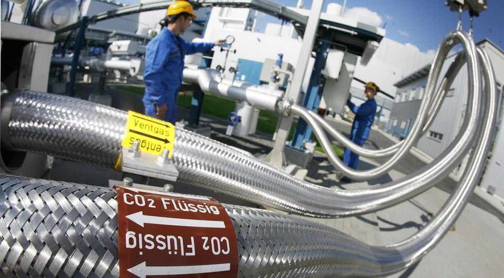 Two employees work on pipes carrying liquid CO2 on September 08, 2008 at the 'Schwarze Pumpe' ('Black Pump') power station run by Europe's biggest power company Vattenfall in Werder near Berlin. (Photo credit MICHAEL URBAN/AFP/Getty Images)