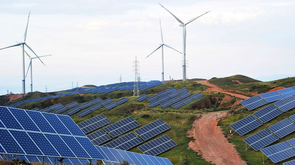 Solar panels and wind turbines are pictured on a mountain at Shenjing Village on July 2, 2018, in Zhangjiakou, China (photo by VCG).