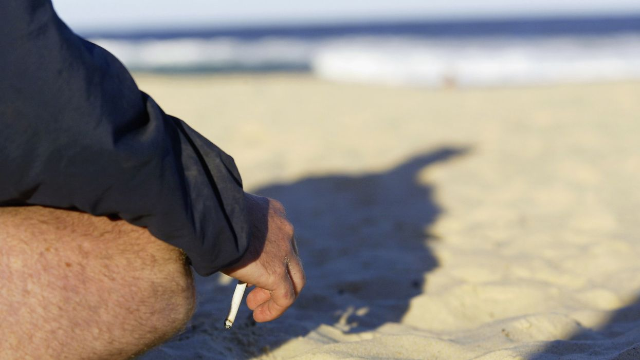 man on beach with smoking cigarette in hand