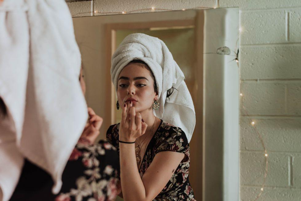 girl fixing make up in mirror
