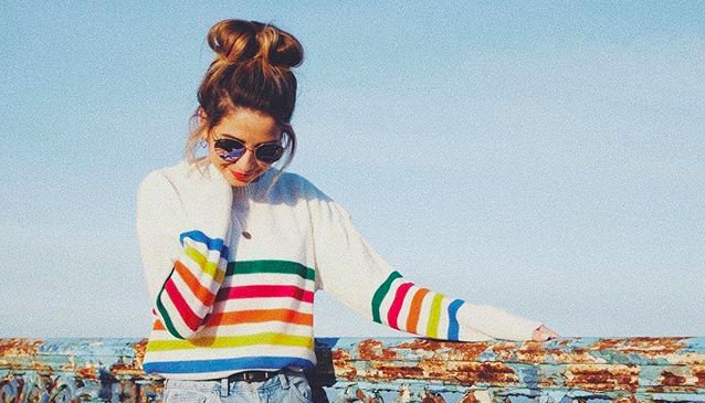 zoella zoe sugg in sunglasses with messy bun posing by railing