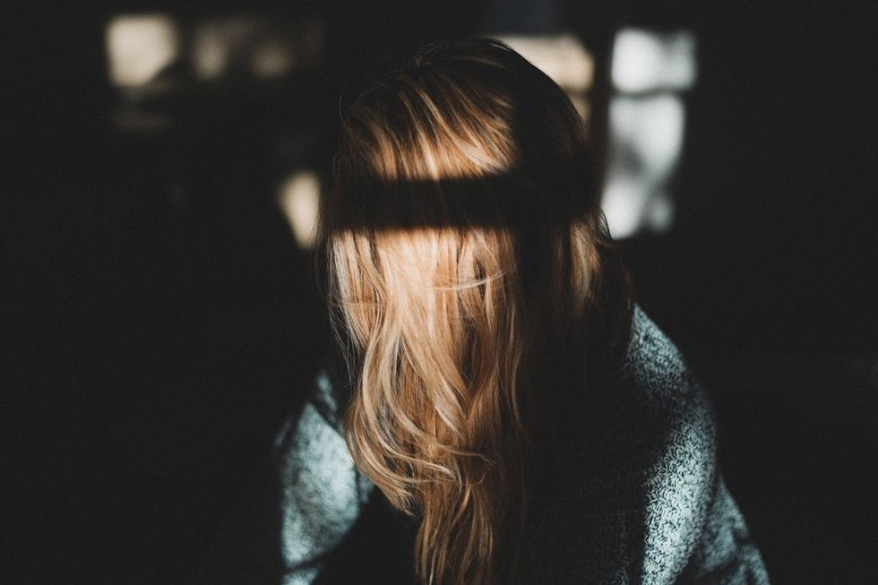 woman alone with shadows from window on hair