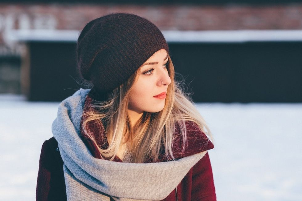 woman in beanie and scarf looking to her side