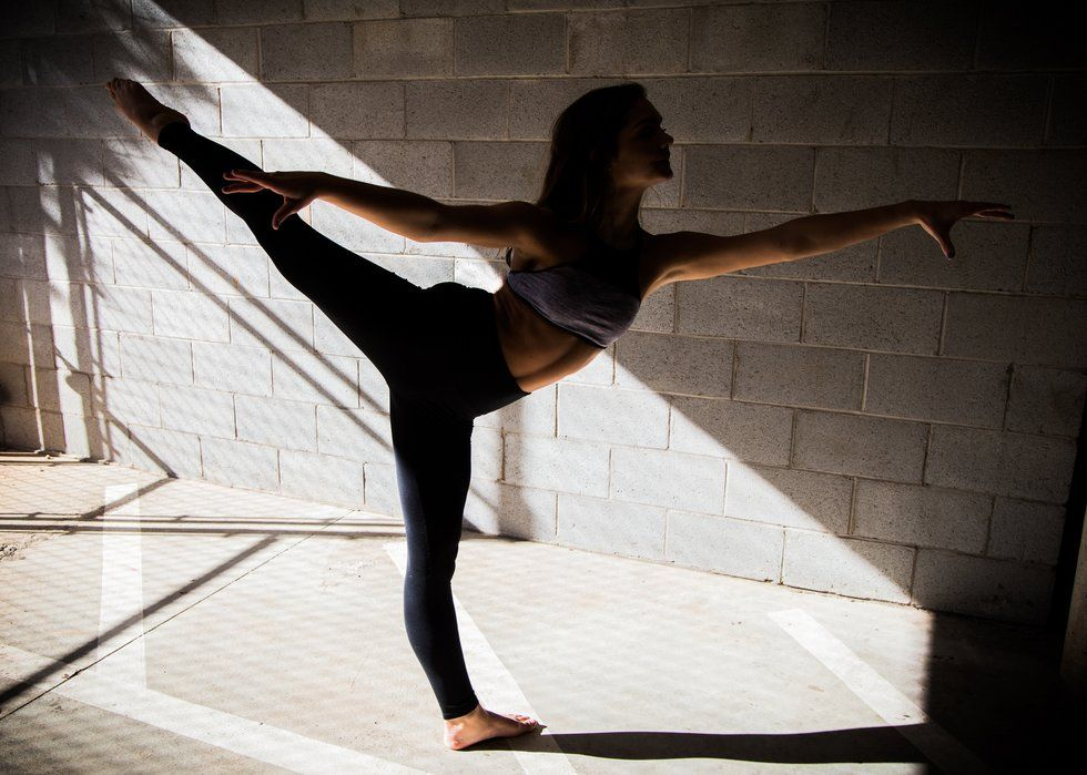 A woman stands in a high first arabesque, with the lower half of her body illuminated by light coming through a window, the rest of her in shadows.