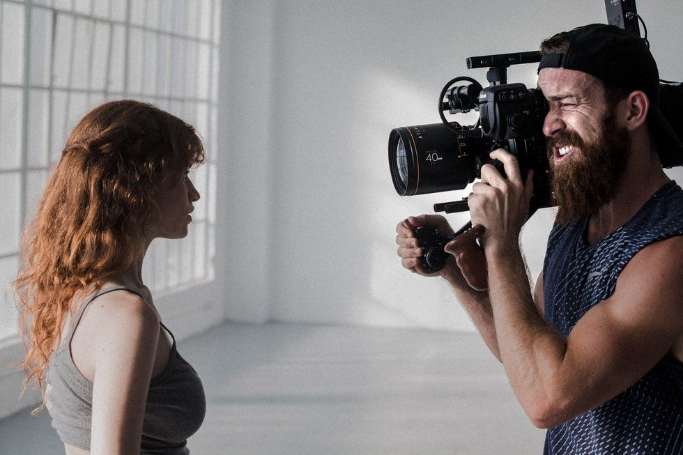 A woman stands facing a camera in an empty room, and a man holds a camera, filming her.