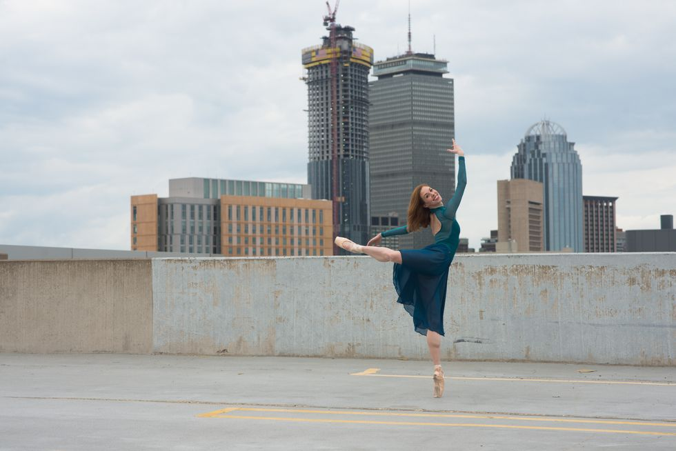Schwan, in a blue long-sleeved leotard, skirt and pointe shoes, stands in back attitude on an urban roof, looking back at the camera and smiling.