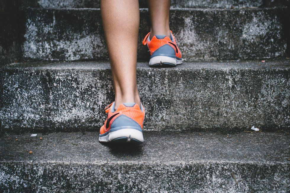 A woman's feet, running up a flight of concrete stairs.