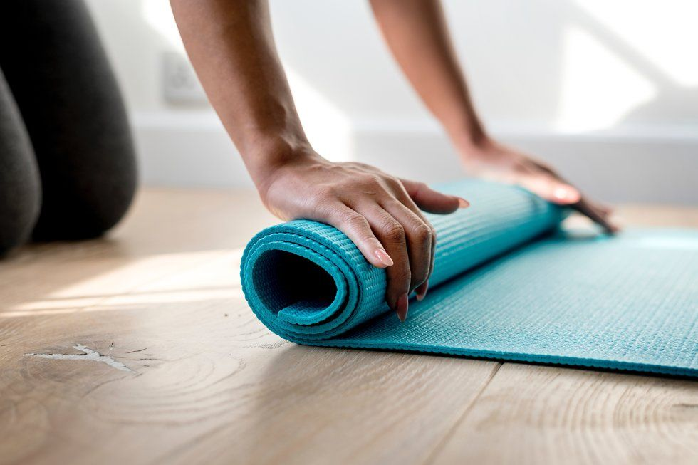 A woman rolling up her blue yoga mat.