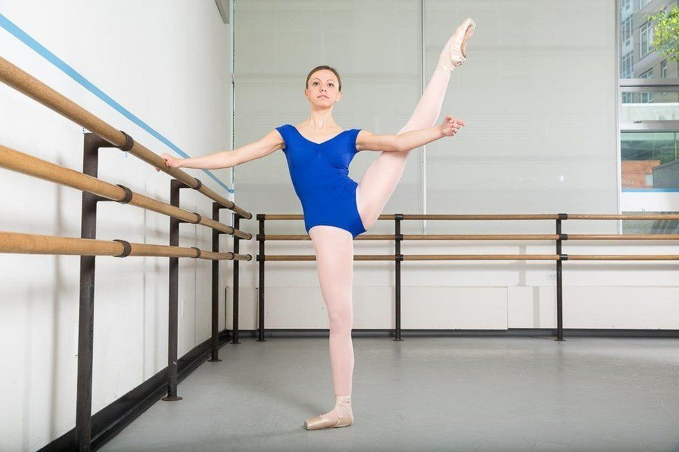 A teenage student extends her leg a la seconde while holding on to the barre.
