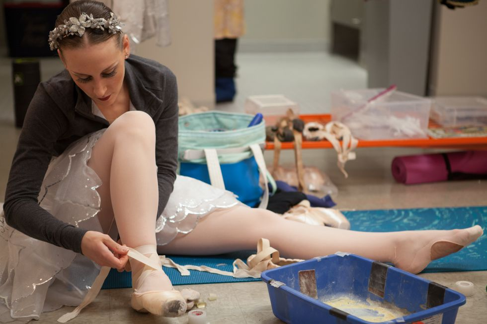 Ballet dancer Chelsea Marie Renner sits on a yoga mat backstage to tie her pointe shoes on. She's wearing a light sweater over her Nutcracker snow costume and has toe tape and a bucket of rosin in front of her.