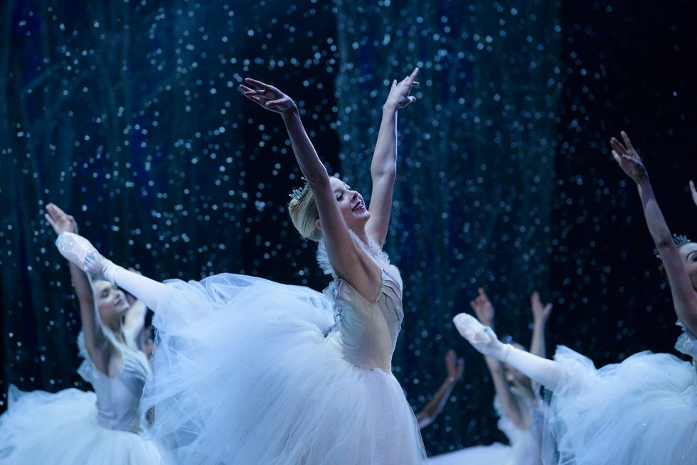 Blonde dancer Dawn Atkins in a high arabesque and bright smile dances Nutcracker's snow scene.