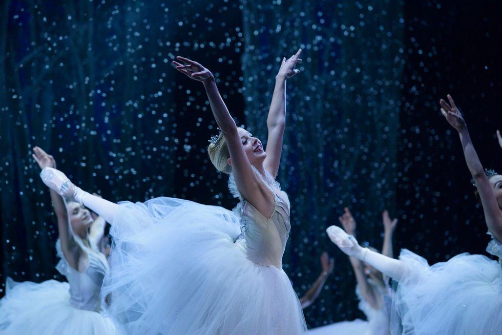 Blonde dancer Dawn Atkins in a high arabesque and bright smile dances Nutcracker's snow scene.