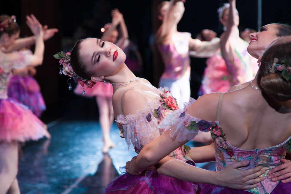 A group of dancers in pink Nutcracker flower costumes hold each other's waists and lean back. Paige Adams, center has her eyes closed.