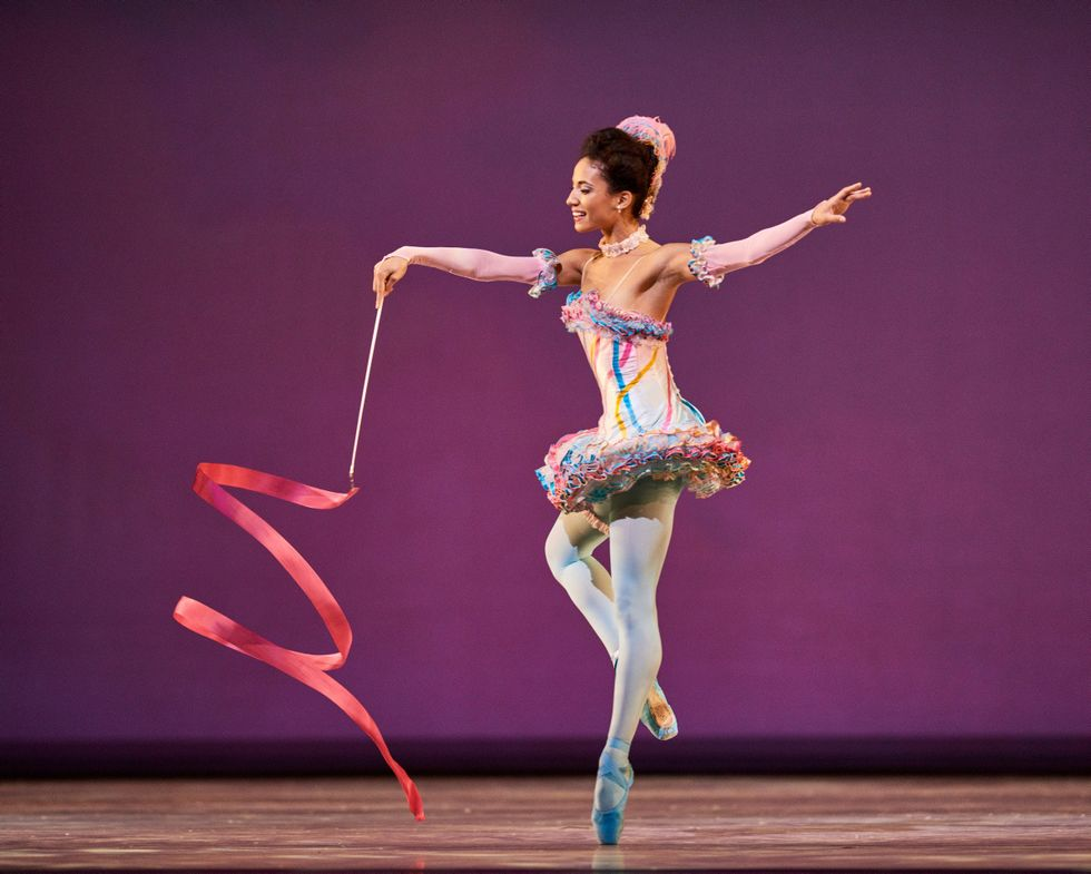 Black ballet dancer Kimberly Marie Olivier stands on pointe with the other foot in coup\u00e9, swirling a pink ribbon.