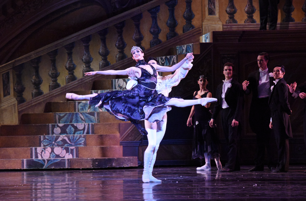 Dancer Jaimi Cullen leaps in a partnered grand jet\u00e9 in Nutcracker's party scene, wearing a black dress.