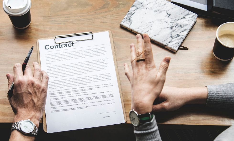 A desk with a clipboard holding an employment contract. There are two people's hands in the photo, one holding a pen. In the background, there are cups of coffee and a notebook.