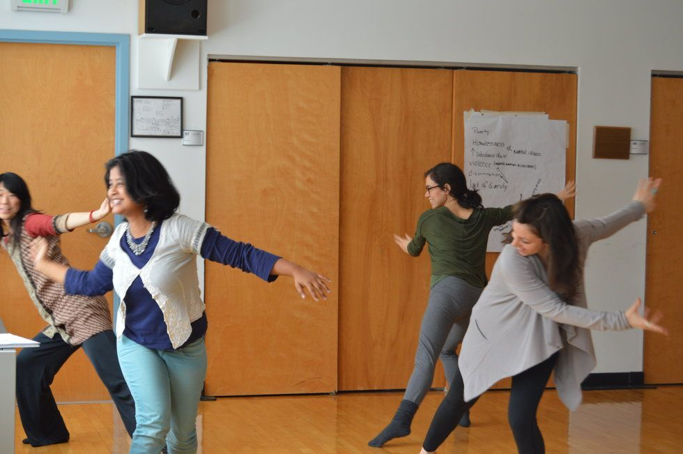 Four women dancing in a classroom.