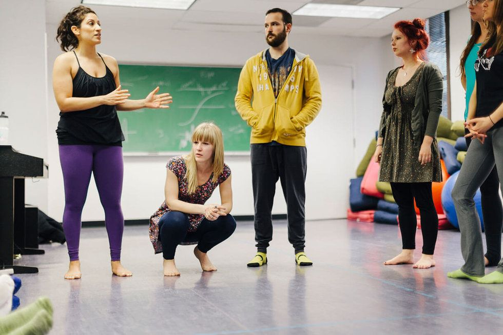 Four students stand barefoot in a dance studio, chatting.