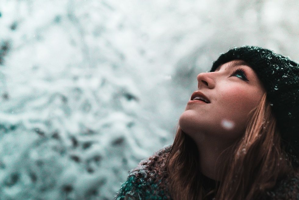 woman standing in the snow looking up at sky