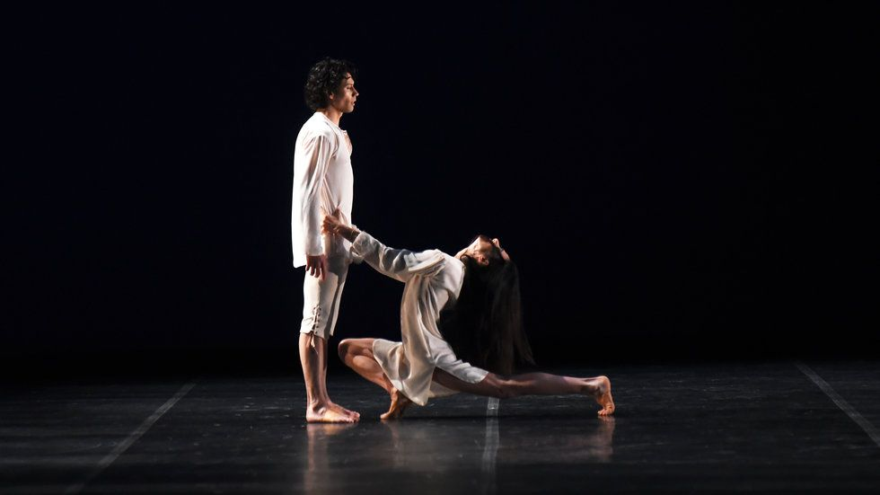 Herman Cornejo stares impassively offstage as Alessandra Ferri lunges deeply at his feet, her hands on his hips and her head arched back.