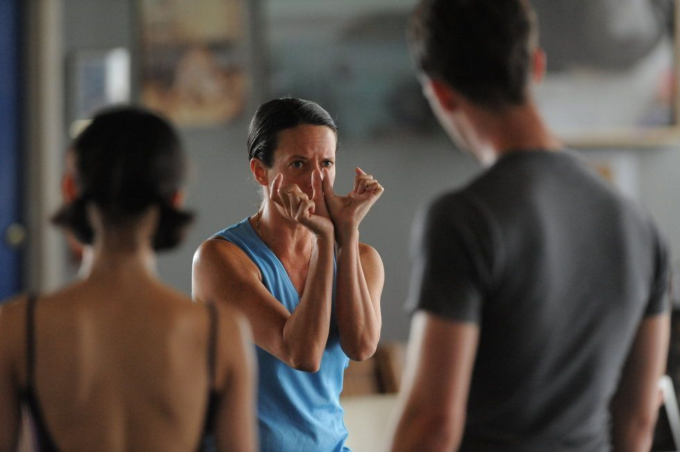 Seiwert, in a blue tank top, demonstrates a gesture to her dancer using both of her hands.