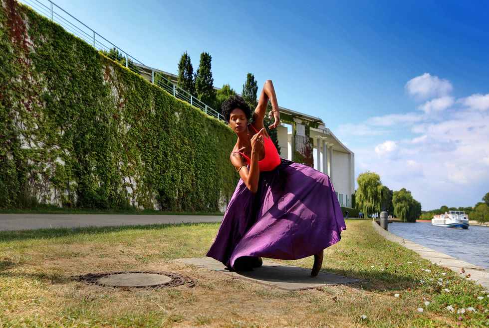 A black dancer squats in a purple skirt along the banks of a river