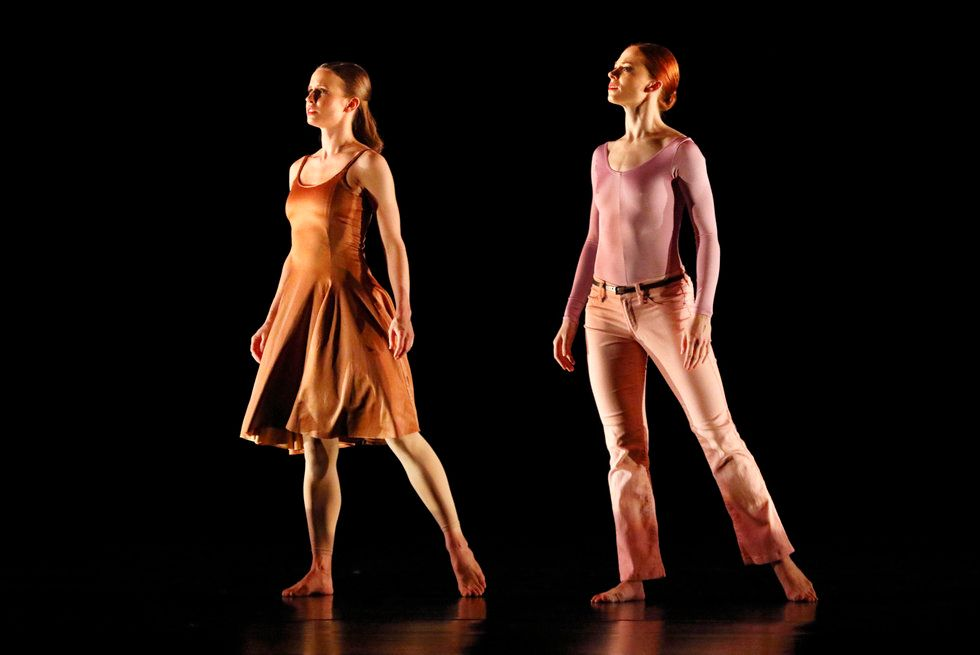 Two women, one in a dress and one in pants and a leotard, look off to the side of a dark stage