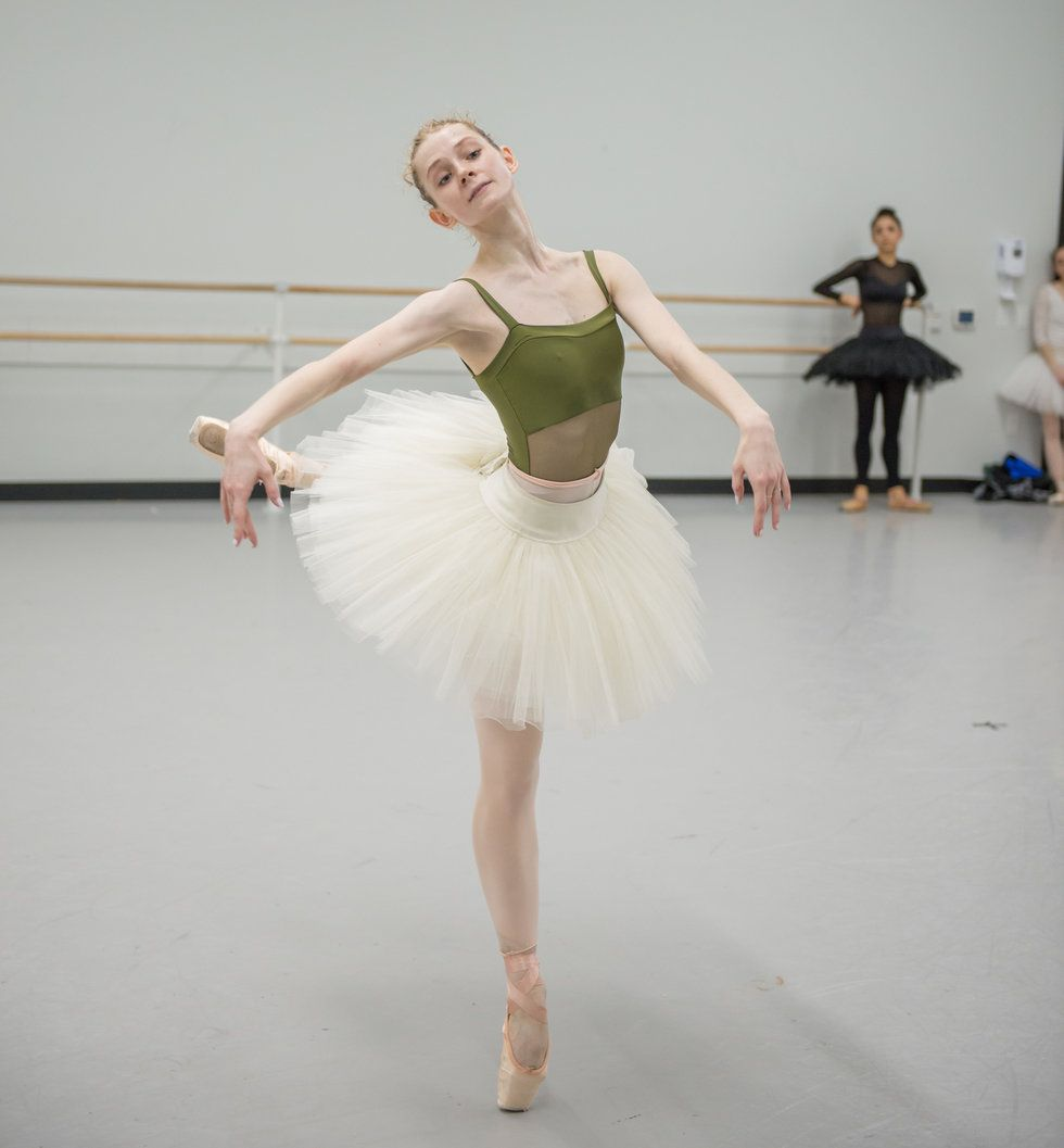 a blond dance in a green leotard and white practice tutu leans into a back attitude in the ballet studio