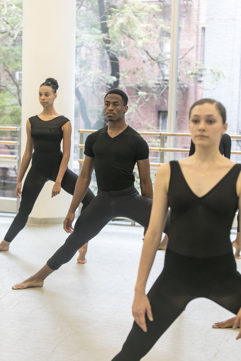 Three dance students in black uniforms stand in a wide second position with one leg bent in plie, arms relaxed at their sides.