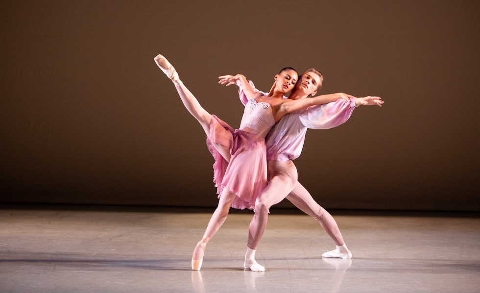 Two dancers in flowy pink ballet costumes partner onstage, the woman on pointe leaning back against her partner's chest, who also supports her with his arms outstretched to the sides underneath hers.