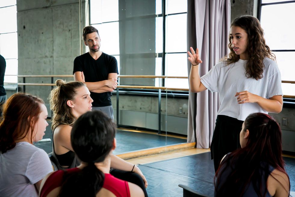 One dancer speaks to a group sitting in chairs, while a teacher looks on