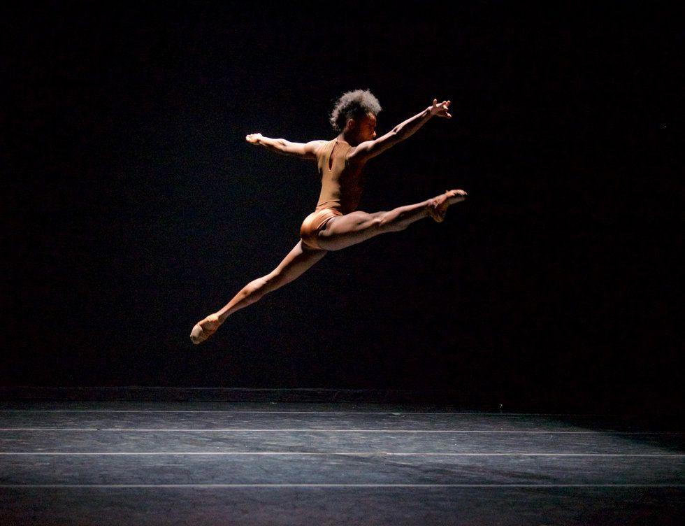 A black dancer flies through the air in a split on a black stage