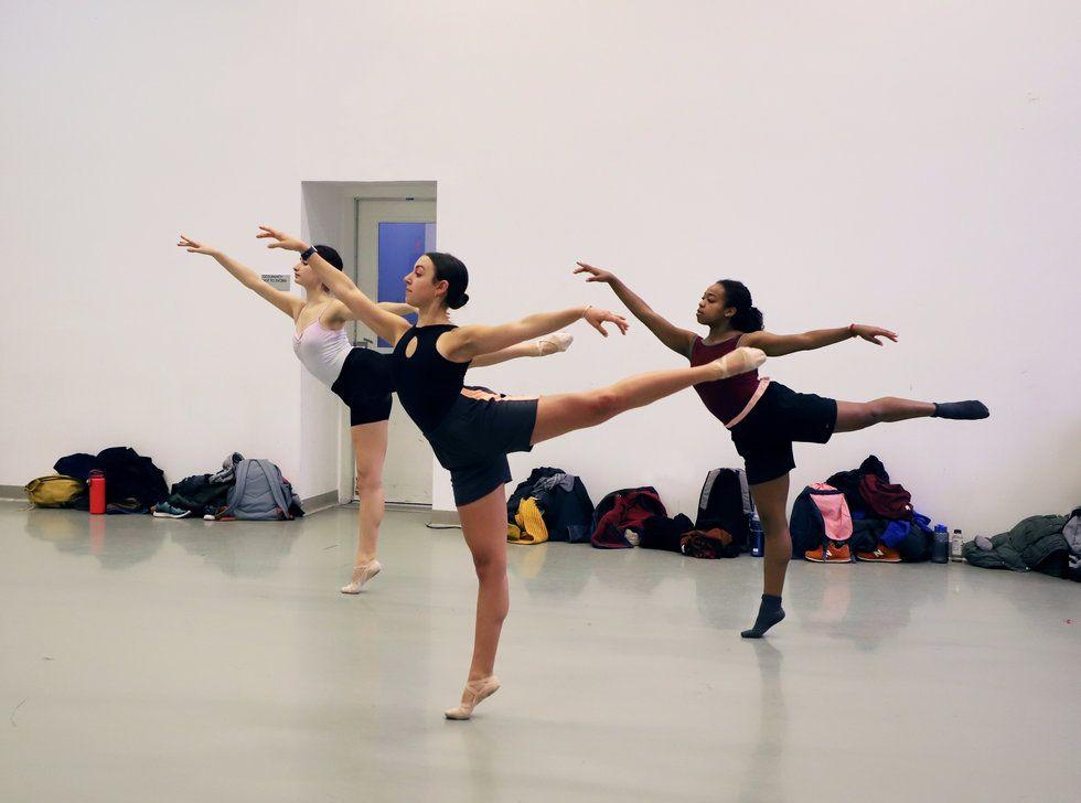 Three female ballet dancers perform arabesque in ballet class