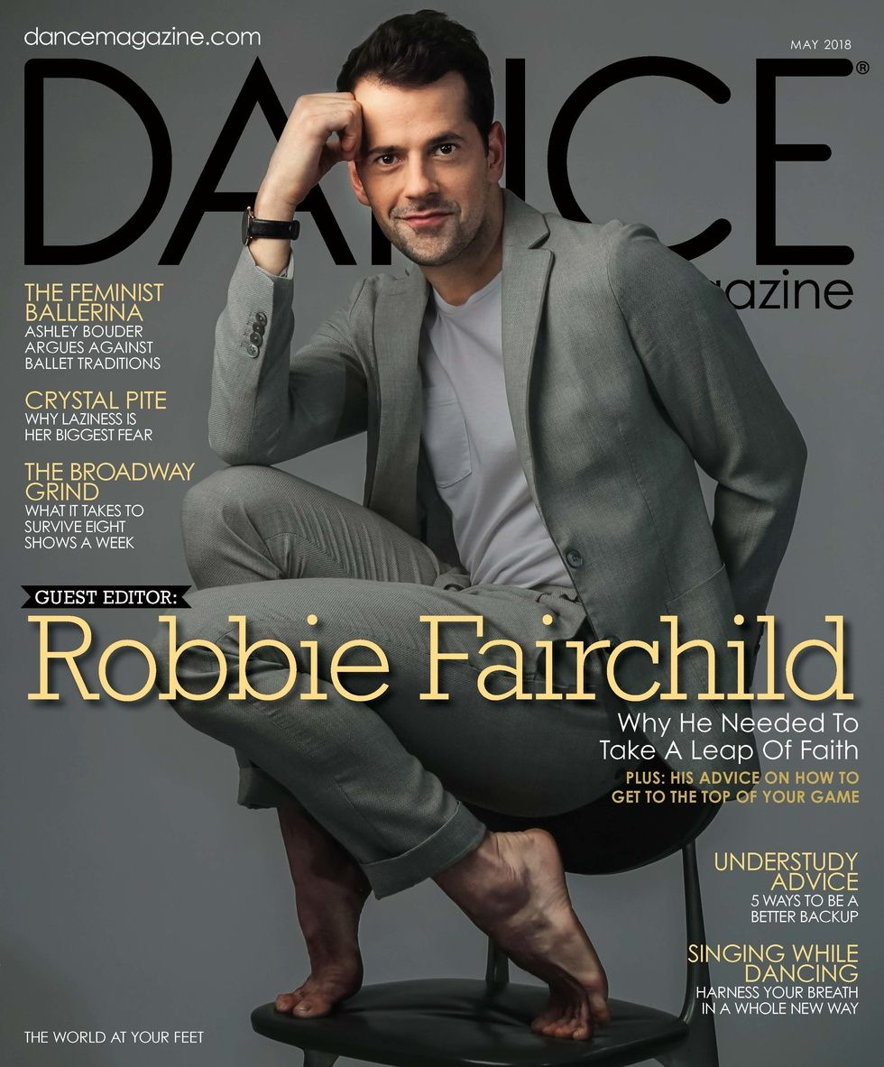 Robbie Fairchild on Dance Magazine's May issue crouches on a chair in a gray suit