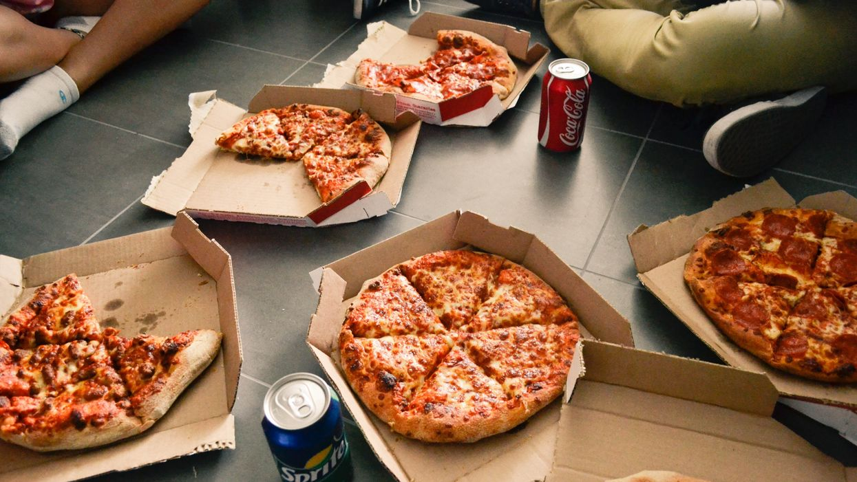 people sitting eating pizza and drinking soda