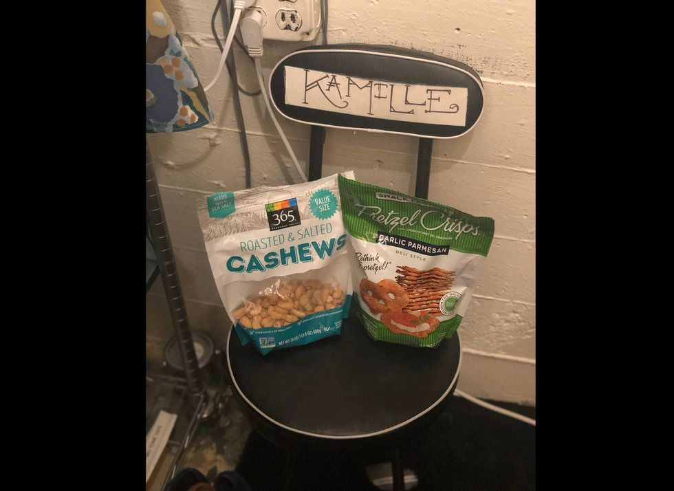 A chair marked Kamille has bags of cashews and pretzels on it